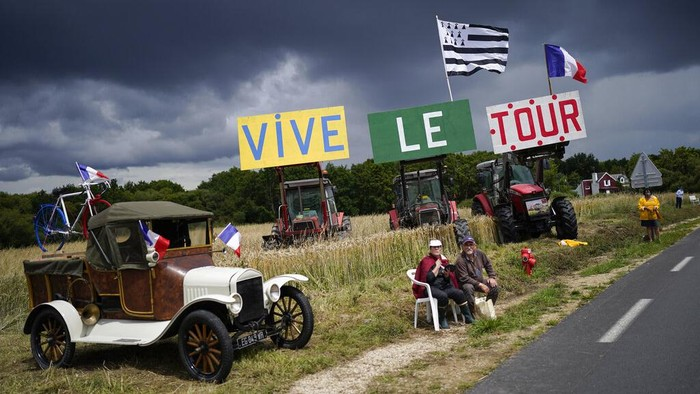 A spectator waits for the pack during the first stage of the Tour de France cycling race over 197.8 kilometers (122.9 miles) with start in Brest and finish in Landerneau, France, Saturday, June 26, 2021. (AP Photo/Daniel Cole)
