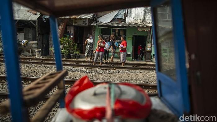 Warga ramai-ramai berjemur di bawah sinar matahari pagi untuk memperkuat sistem imun. Selain di tanah lapang, warga juga berjemur di jalur perlintasan kereta api di Jakarta.