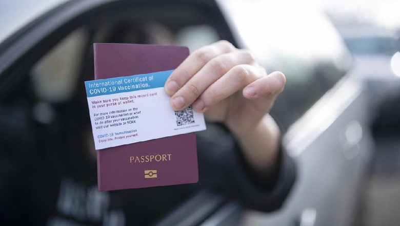 Unrecognisable person in car giving on border control passport and certificate of covid-19 vaccination.