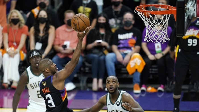 Phoenix Suns guard Chris Paul (3) scores as Milwaukee Bucks forward Khris Middleton (22) and Bucks guard Jrue Holiday, left, look on during the second half of Game 1 of basketballs NBA Finals, Tuesday, July 6, 2021, in Phoenix. (AP Photo/Ross D. Franklin)