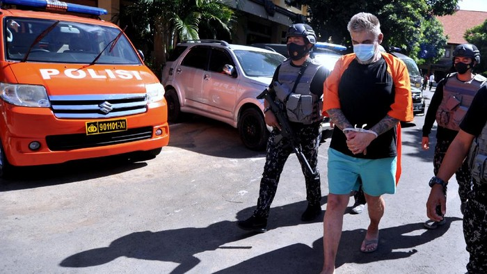 Petugas kepolisian menghadirkan tersangka Warga Negara Rusia berinisial EB (kanan) saat konferensi pers di Polda Bali, Denpasar, Bali, Selasa (6/7/2021). EB mengaku sebagai anggota Interpol untuk memeras dan mengancam korbannya yaitu seorang pengusaha asing asal Uzbekistan yang tinggal di Bali sehingga korban ketakutan dan menyerahkan sebanyak 22 unit sepeda motor serta uang sebesar Rp121 juta kepada tersangka. ANTARA FOTO/Fikri Yusuf/pras.