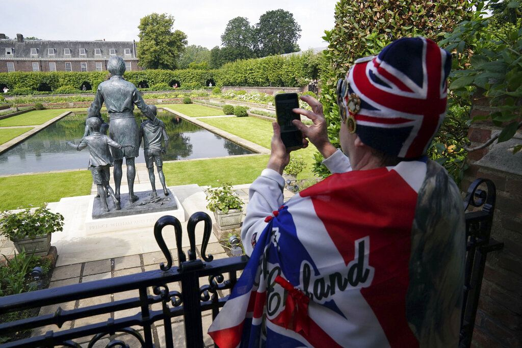 The gates are opened to allow people to see the statue of Diana, Princess of Wales, a day after its unveiling, in the Sunken Garden at Kensington Palace, London, Friday July 2, 2021. The statue, which shows a larger-than-life Diana surrounded by three children, was commissioned by Prince William and Prince Harry in 2017.