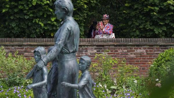 Warga melihat patung Diana, Princess of Wales, di Taman Sunken di Istana Kensington, London. AP Photo/Jonathan Brady