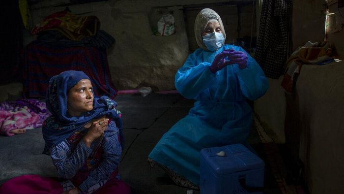 """Masrat Farid, a healthcare worker, prepares to administer a dose of Covishield vaccine to Rubia Begum inside a hut during a COVID-19 vaccination drive in Gagangeer, northeast of Srinagar, Indian controlled Kashmir on June 22, 2021. Farid has traveled long distances to vaccinate mostly shepherds and nomadic herders in the remote meadows of the Himalayan region of Indian-controlled Kashmir. Her challenge has not been the treacherous terrain but to persuade women to get COVID-19 vaccines. """"Everywhere we go it seems rumors reach earlier than we do, and it makes our job difficult,"""" Farid said recently during a vaccination campaign at a high altitude meadow. (AP Photo/Dar Yasin)"""