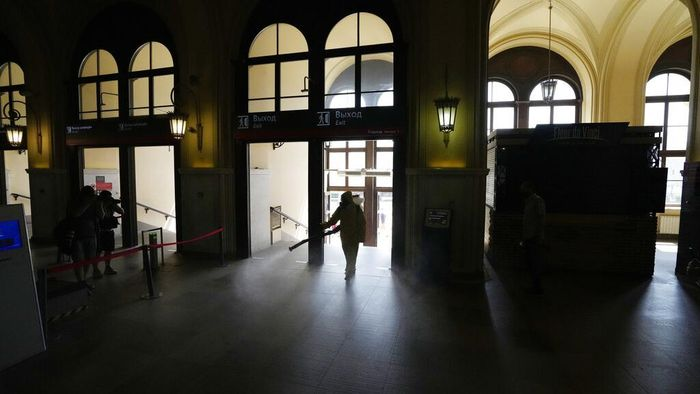 An employee of the Federal State Center for Special Risk Rescue Operations of Russia Emergency Situations disinfects a hall of Leningradsky railway station in Moscow, Russia, Thursday, June 24, 2021. Coronavirus infections continue to soar in Russia, with the highest reported new cases and further deaths since late January. (AP Photo/Pavel Golovkin)