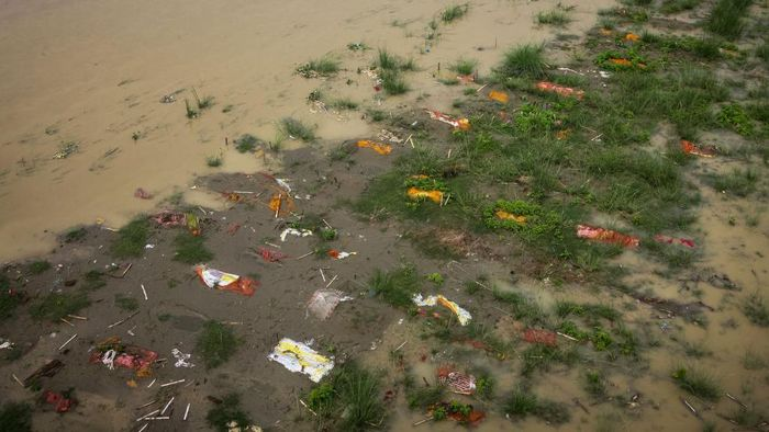 ALLAHABAD, INDIA - JUNE 28: Bodies, many of which are believed to be COVID-19 victims, are seen partially exposed in shallow sand graves as rainwater inundated the site and caused the soil to be washed away at a cremation ground on the banks of the Ganges River on June 28, 2021 in Phaphamau, near Prayagraj (also known as Allahabad), Uttar Pradesh, India. India has seen a steady fall in its COVID-19 infection numbers in June. Many states and cities have made steps towards re-opening fully, though the number of people vaccinated as a share of the overall population remains low and experts raise concerns that re-opening too quickly could once again risk recent gains made in fighting the coronavirus. India also successfully vaccinated up to 8 million people a day in the last week, as the government picks up the pace and announced plans to vaccinate all adults by the end of the year. (Photo by Ritesh Shukla/Getty Images)