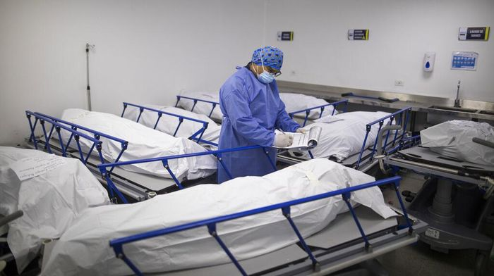 A health worker records the information of patients who died of complications related to COVID-19, at the morgue of the Regional Hospital in Zipaquira, Colombia, Monday, June 28, 2021. Colombia has become a pandemic hotspot as it experiences a third wave of COVID-19 infections and a surge in deaths. (AP Photo/Ivan Valencia)
