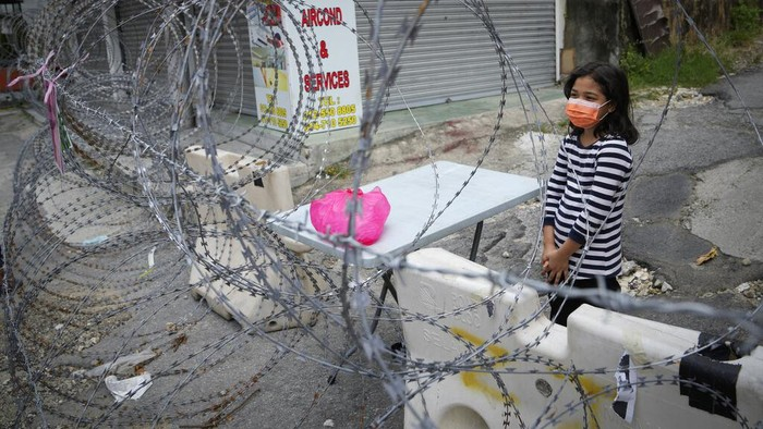 A resident, left, receives food from a delivery man through barbwire at Segambut Dalam area placed under the enhanced movement control order (EMCO) due to drastic increase in the number of COVID-19 cases recorded in Kuala Lumpur, Malaysia, Sunday, July 4, 2021. Malaysia starts further tightening movement curbs and imposes a curfew in most areas in its richest state Selangor and parts of Kuala Lumpur, where coronavirus cases remain high despite a national lockdown last month. (AP Photo/Vincent Thian)