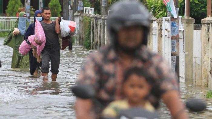 Sejumlah warga menyelamatkan barang-barang berharga saat banjir melanda di Desa Lampasie Engking, Kecamatan Darul Imarah, Aceh Besar, Aceh, Jumat (9/7/2021). Banjir yang disebabkan tingginya intensitas hujan itu mengakibatkan puluhan rumah warga terendam banjir dengan ketinggian air 30 cm - 90 cm dan sebagian warga terpaksa mengungsi kerumah tetangganya. ANTARA FOTO/Syifa Yulinnas/foc.