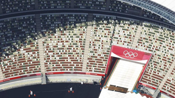 In this aerial photo, the Olympic Rings are seen with spectators' seats at the National Stadium in Tokyo Japan, Monday, June 21, 2021. Fans will be banned from Tokyo-area stadiums and arenas when the Olympics begin in two weeks, the city's governor said Thursday after meeting with organizers of the pandemic-postponed games.(Kyodo News via AP)