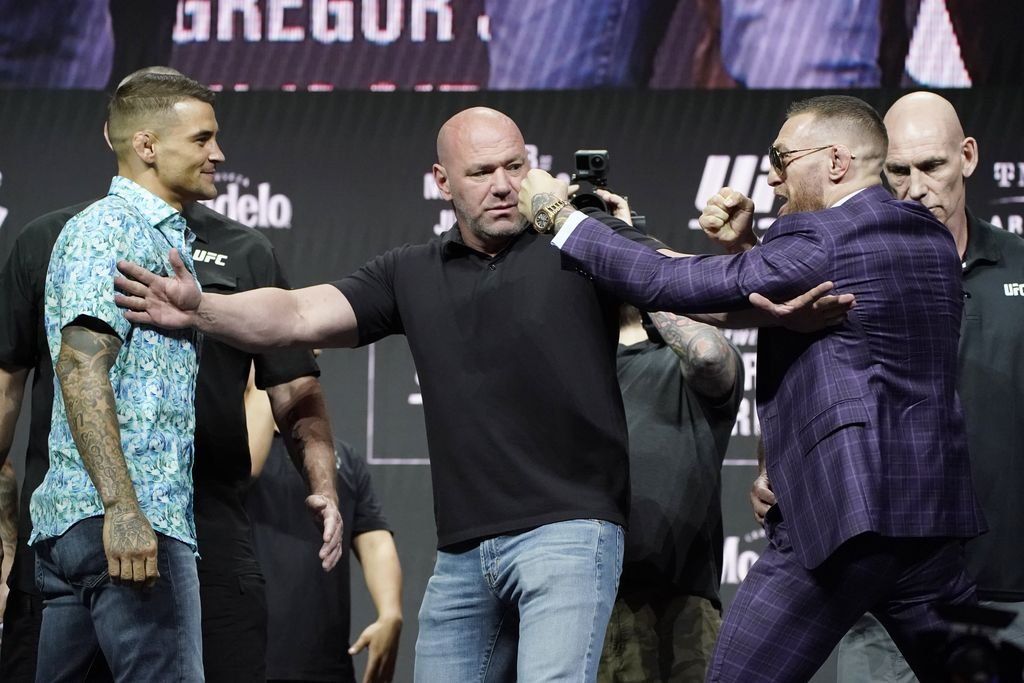 Conor McGregor, right, kicks at Dustin Poirier, left, as Dana White, UFC President, holds them apart during a news conference for a UFC 264 mixed martial arts bout Thursday, July 8, 2021, in Las Vegas. (AP Photo/John Locher)