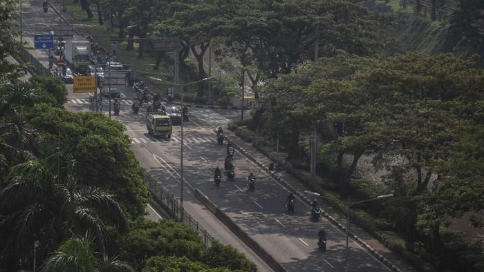 Petugas PT Pos Indonesia melintasi di kawasan Kebon Kacang, Jakarta, Jumat (9/7/2021). Polda Metro Jaya mencatat selama penerapan PPKM Darurat Jawa-Bali mobilitas warga di Ibu Kota mengalami penurunan lebih dari 50 persen dari kondisi biasanya. ANTARA FOTO/Aprillio Akbar/foc.