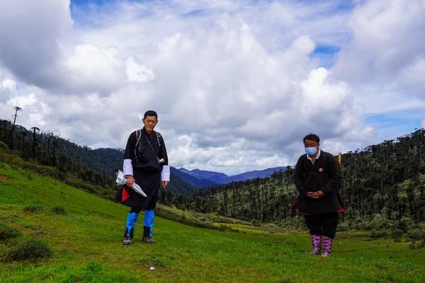 Raja Jigme Khesar Namgyel Wangchuck memakai topi bisbol, jubah tradisional Gho selutut, dan tas punggung untuk menulusuri hutan hingga gunung. (His Majesty King Jigme Khesar Namgyel Wangchuck/Facebook)