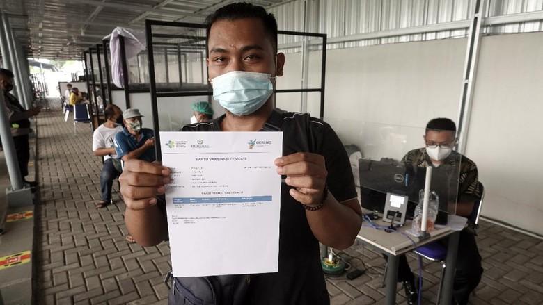 Calon penumpang kereta api menunjukan kartu vaksin yang diperoleh usai, melakukan vaksinasi COVID-19 di Stasiun Purwokerto, Banyumas, Jateng, Jumat (9/7/2021). PT. KAI Daop V Purwokerto menyediakan layanan vaksinasi COVID-19 gratis bagi pelanggan kereta api jarak jauh di sejumlah stasiun keberangkatan, untuk membantu melengkapi persyaratan perjalanan selama masa PPKM darurat. ANTARA FOTO/Idhad Zakaria/hp.