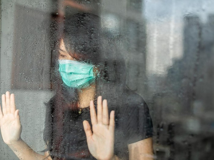 Young woman in isolation at home for coronavirus  looking out of window during rain
