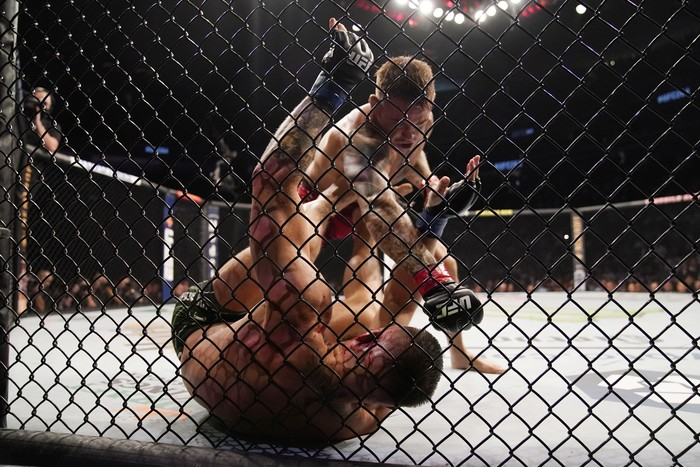 Conor McGregor sits on the mat after an injury during his lightweight mixed martial arts bout with Dustin Poirier at UFC 264 on Saturday, July 10, 2021, in Las Vegas. (AP Photo/John Locher)