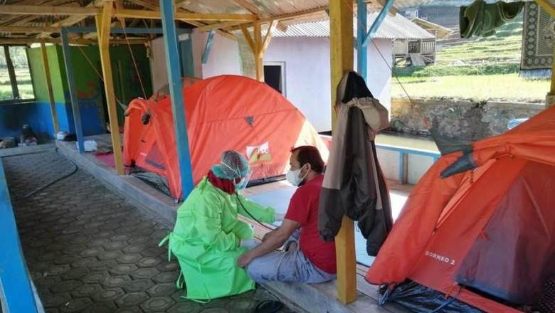Petugas medis memeriksa kondisi kesehatan warga yang terpapar wabah COVID-19 di tempat isolasi mandiri kawasan wisata alam River Tubing, Leuwi Paranje Bojong, Kecamatan Banjarwangi, Kabupaten Garut, Jumat (9/7/2021).