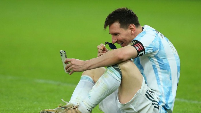 RIO DE JANEIRO, BRAZIL - JULY 10: Lionel Messi of Argentina celebrates as he talks on his phone with his family after winning the final of Copa America Brazil 2021 between Brazil and Argentina at Maracana Stadium on July 10, 2021 in Rio de Janeiro, Brazil. (Photo by Alexandre Schneider/Getty Images)