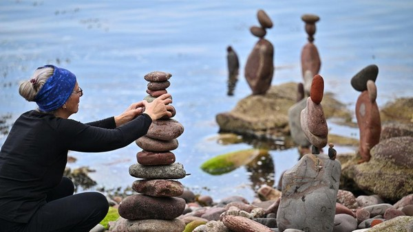 Para seniman dengan lihainya menyusun batu-batu yang beragam ukuran.
