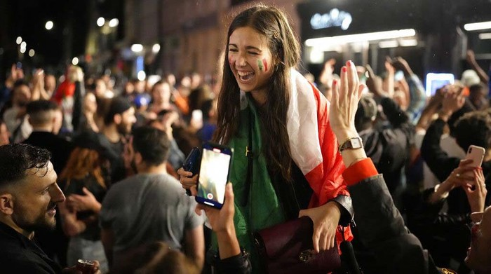 Italy supporters celebrate in Soho, London's West End, Sunday, July 11, 2021, after Italy won the Euro 2020 soccer championship final match between England and Italy played at Wembley Stadium. (AP Photo/Matt Dunham)