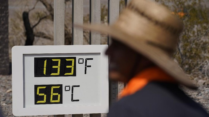 People visit a thermometer Sunday, July 11, 2021, in Death Valley National Park, Calif. Death Valley in southeastern Californias Mojave Desert reached 128 degrees Fahrenheit (53 Celsius) on Saturday, according to the National Weather Services reading at Furnace Creek. The high temperature was actually lower than the previous day, when the location reached 130 F (54 C). (AP Photo/John Locher)