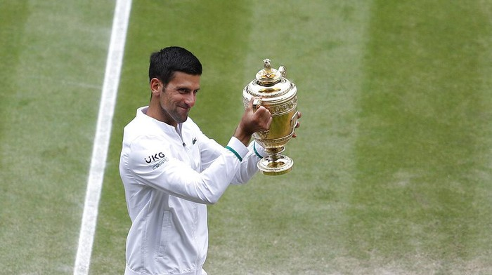 Serbias Novak Djokovic shows off the winners trophy to the crowd as he walks around Centre Court after defeating Italys Matteo Berrettini in the mens singles final on day thirteen of the Wimbledon Tennis Championships in London, Sunday, July 11, 2021. (Pete Nichols/Pool Via AP)