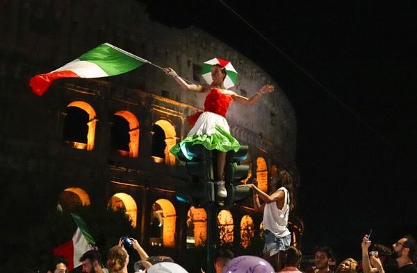 Salah satu tempat yang dijadikan tempat perayaan adalah Colosseum, Roma. Landmark Italia itu dipadati ratusan orang sambil mengibarkan bendera dan menyalakan flare. Foto: AP Photo