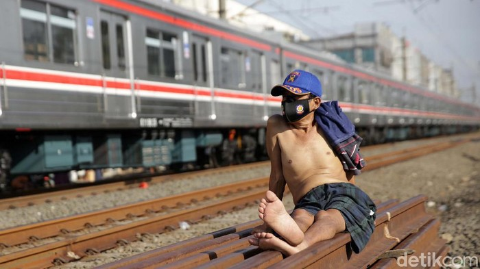 Di tengah meningkatnya kasus COVID-19, warga berjemur dibantaran rel kereta api. Hal ini guna meningkatkan imunitas tubuh.