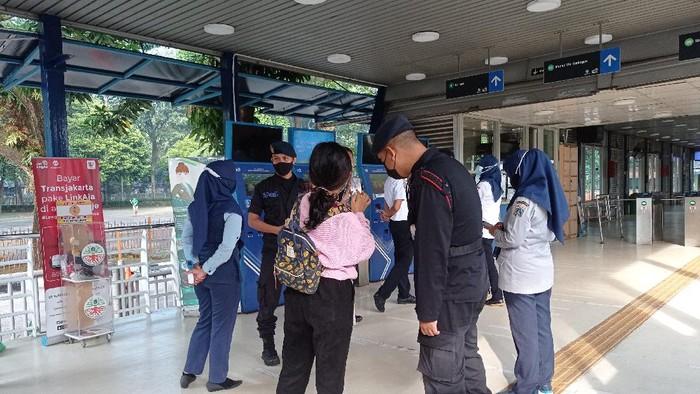 Calon Penumpang Tunjukkan STRP ke Petugas di Halte TransJ