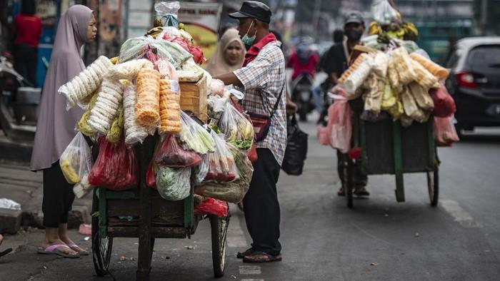 Pedagang melayani pembeli di los buah dan sayuran Pasar Legi Parakan, Temanggung, Jawa Tengah, Selasa (13/7/2021). Pedagang mengaku omzet penjualan menurun hingga 50 persen sejak Pemberlakuan Pembatasan Kegiatan Masyarakat (PPKM) Darurat karena operasional pasar hanya sampai jam 14.00 WIB. ANTARA FOTO/Anis Efizudin/wsj.