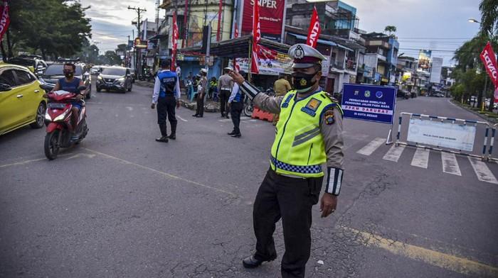 Petugas gabungan dari Kepolisian dan Satpol PP membubarkan pengendara roda dua yang berkumpul saat pemberlakuan Pembatasan Kegiatan Masyarakat (PPKM) Darurat di Kawasan Kesawan, Medan, Sumatera Utara, Senin (12/7/2021) malam. Razia tersebut bertujuan untuk mengendalikan penyebaran COVID-19 selama masa PPKM darurat di Medan. ANTARA FOTO/Fransisco Carolio/Lmo/wsj.