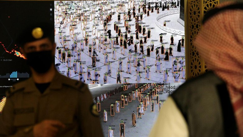 Saudi security personnel watch smart screens, which identify passing pilgrims authorization to participate in the Hajj, at al Zaidy pilgrims reception center in Mecca, ahead of the upcoming annual pilgrimage, Monday, July 12, 2021. The pilgrimage to Mecca required once in a lifetime of every Muslim who can afford it and is physically able to make it, used to draw more than 2 million people. But for a second straight year it has been curtailed due to the coronavirus with only vaccinated people in Saudi Arabia able to participate. (AP Photo/Amr Nabil)