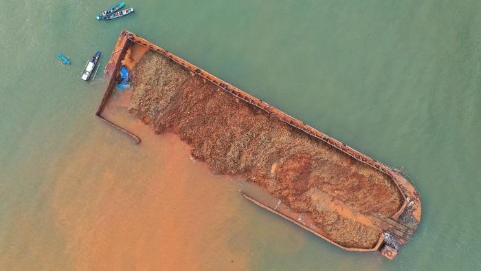 Sebuah kapal tongkang berisi nikel dalam kondisi nyaris terbalik di bibir Pantai Batu Gong, Konawe, Sulawesi Tenggara, Selasa (13/7/2021). Hal tersebut terjadi karena diduga tali kapal tongkang putus saat dihantam ombak besar disertai angin kencang tidak jauh dari pubrik pemurnikaan nikel VDNI, sementara pemilik kapal tongkang yang mengakibatkan pencemaran di wilayah tersebut belum diketahui identitasnya. ANTARA FOTO/Jojon/aww.
