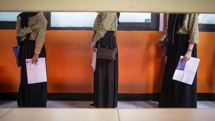 Vaksinator menyuntikkan vaksin COVID-19 Sinovac kepada pelajar di SMAN 1 Kota Tangerang, Banten, Rabu (14/7/2021). Badan Intelejen Negara (BIN) Provinsi Banten bersama Pemerintah Kota Tangerang menggelar vaksinasi untuk pelajar dengan target sebanyak 1.000 pelajar guna mendukung program percepatan vaksinasi nasional. ANTARA FOTO/Fauzan/foc.