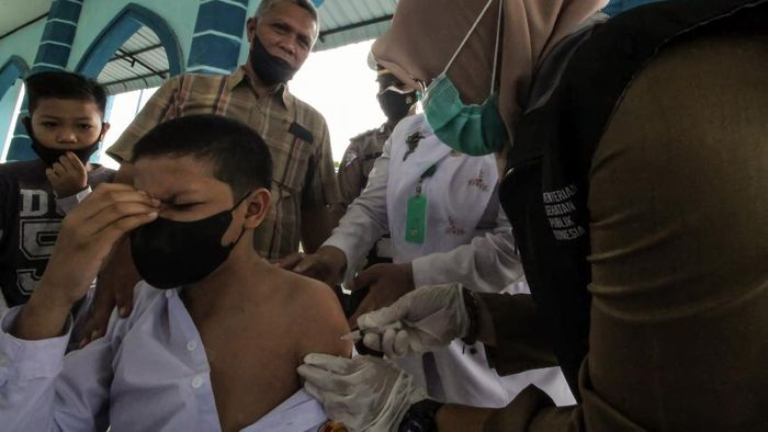 Petugas kesehatan menyuntikkan vaksin COVID-19 kepada seorang pelajar remaja di Lhokseumawe, Aceh, Senin (12/7/2021). Vaksinasi dosis pertama dengan target vaksinasi 100 remaja dari usia 12-17 tahun tersebut dalam rangka percepatan vaksinasi sekaligus mendukung program satu juta vaksin COVID-19 per hari. ANTARA FOTO/Rahmad/aww.