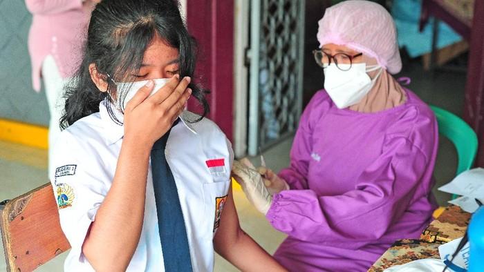 Pelajar SMPN 1 Kota Jambi menerima suntikan vaksin COVID-19 dosis pertama dari tenaga kesehatan di Jambi, Senin (12/7/2021). Pemerintah Kota Jambi mulai melaksanakan vaksinasi massal untuk pelajar atau anak usia 12-17 tahun yang diawali di SMPN 1 kota itu guna mendukung optimalisasi perpanjangan PPKM Mikro yang telah dimulai sejak 6-20 Juli 2021. ANTARA FOTO/Wahdi Septiawan/aww.