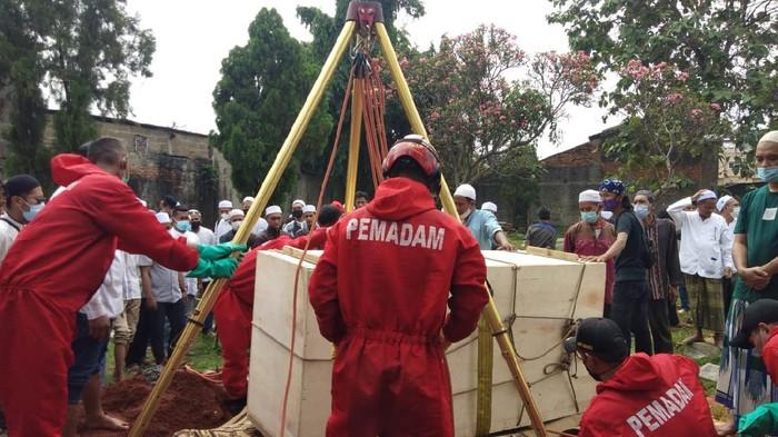 Petugas Damkar Jaktim membantu proses pemakaman jenazah seberat 300 kg di Duren Sawit, Jakarta Timur.