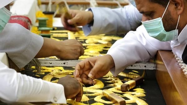 Sejumlah pekerja tampak mengenakan masker guna mencegah penyebaran virus Corona saat tengah menyelesaikan pembuatan kiswah di Makkah, Arab Saudi.