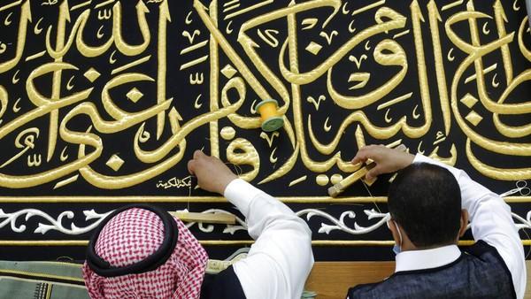 Dua orang pekerja sedang menyulam kaligrafi Islam saat tengah menyelesaikan pembuatan kiswah di pabrik Kiswah yang berada di Makkah, Arab Saudi, Rabu (14/7/2021).