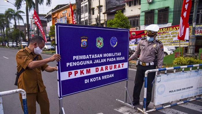 Personel Kepolisian memasang rambu penyekatan Pemberlakuan Pembatasan Kegiatan Masyarakat (PPKM) Darurat di Pertigaan Simpang Kampus USU, Medan Baru, Kota Medan, Sumatera Utara, Senin (12/7/2021). Penyekatan tersebut dalam rangka mengurangi mobilitas warga demi mengurangi angka penyebaran COVID-19 selama pemberlakuan PPKM Darurat di Kota Medan. ANTARA FOTO/Fransisco Carolio/Lmo/foc.
