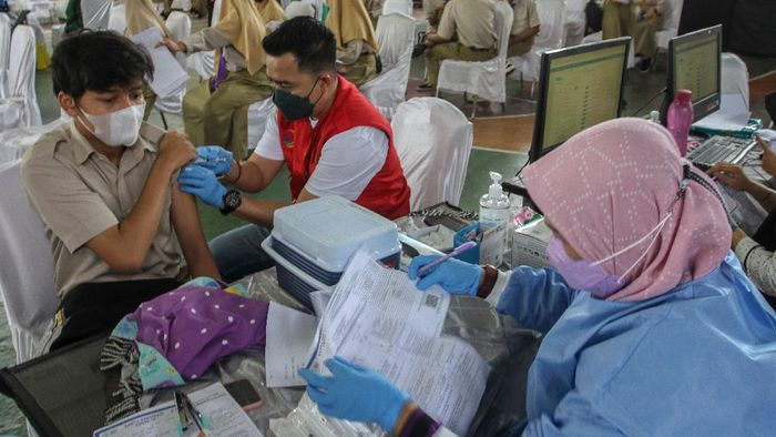 Seorang pelajar memperlihatkan kartu vaksinasi usai mendapatkan suntikkan vaksin COVID-19 di SMAN 1 Kota Pekanbaru, Riau, Rabu (14/7/2021). Pemerintah Provinsi Riau bersama Badan Intelijen Negara (BIN) menggelar vaksinasi massal untuk pelajar untuk mendukung serta mempercepat program vaksinasi nasional. ANTARA FOTO/Rony Muharrman/foc.