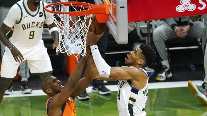 Milwaukee Bucks forward Giannis Antetokounmpo shoots over Phoenix Suns guard Chris Paul, left, during the second half of Game 4 of basketballs NBA Finals in Milwaukee, Wednesday, July 14, 2021. (AP Photo/Paul Sancya)