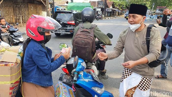 YouTuber Ustaz Ujang Busthomi bagikan uang ke pengendara motor.
