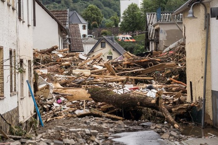 A man walks past a car immersed in debris after floods caused major damage in Hagen, western Germany, on July 15, 2021. - Heavy rains and floods lashing western Europe have killed at least 42 people in Germany and left many more missing, as rising waters led several houses to collapse. (Photo by INA FASSBENDER / AFP)
