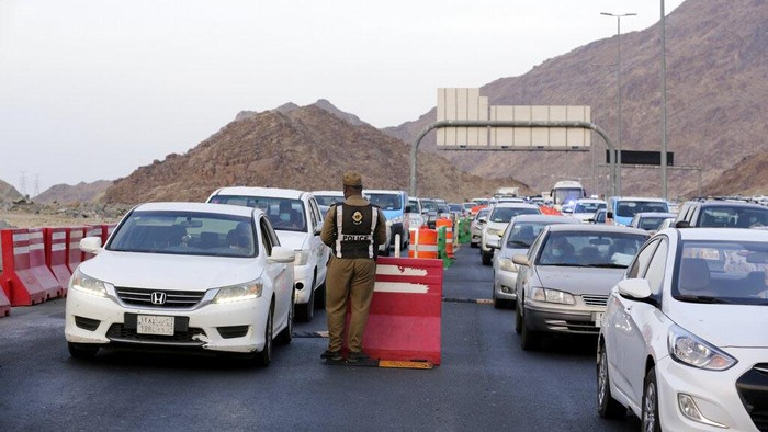 A Saudi policeman checks vehicles at a check point at the Muslim holy city of Mecca, ahead of the upcoming annual hajj pilgrimage, Thursday, July 15, 2021. The pilgrimage to Mecca required once in a lifetime of every Muslim who can afford it and is physically able to make it, used to draw more than 2 million people. But for a second straight year it has been curtailed due to the coronavirus with only vaccinated people in Saudi Arabia able to participate. (AP Photo/Amr Nabil)