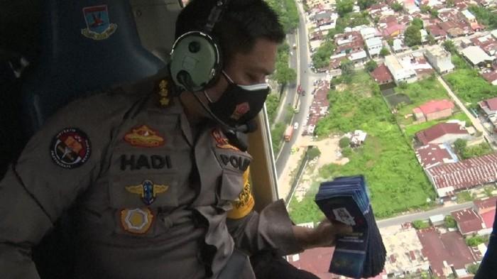 Kabid Humas Polda Sumut Kombes Hadi Wahyudi saat menebar brosur dari helikopter (dok Humas Polda Sumut)
