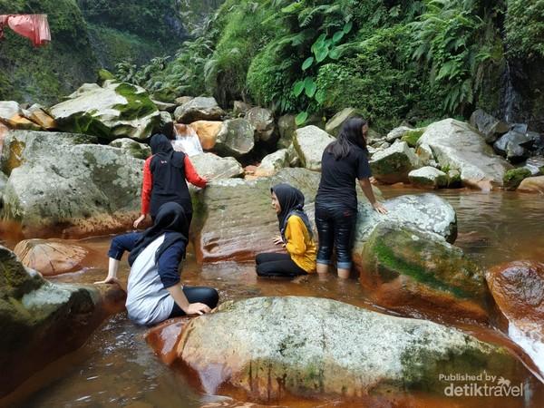 pengunjung sedang berenang menikmati sejuknya sungai