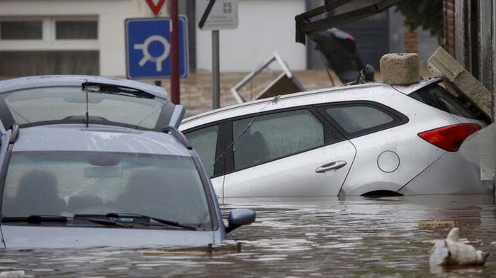 Cars are nearly submerged as floodwaters run down a main street in Pepinster, Belgium, Thursday, July 15, 2021. Heavy rainfall is causing flooding in several provinces in Belgium with rain expected to last until Friday. (AP Photo/Olivier Matthys)