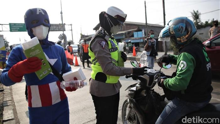 Pemandangan unik terlihat di kawasan Tambun, Kabupaten Bekasi, hari ini. Sejumlah relawan membagikan makanan dengan mengenakan kostum superhero.