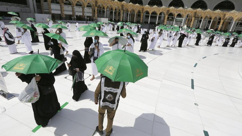 A Saudi police woman, left, who is recently deployed to the service, at top left, stands alert in front of the Al-Safa mountain, as pilgrims pray at the Grand Mosque, at the Grand Mosque, a day before the annual hajj pilgrimage, Saturday, July 17, 2021. The pilgrimage to Mecca required once in a lifetime of every Muslim who can afford it and is physically able to make it, used to draw more than 2 million people. But for a second straight year it has been curtailed due to the coronavirus with only vaccinated people in Saudi Arabia able to participate. (AP Photo/Amr Nabil)